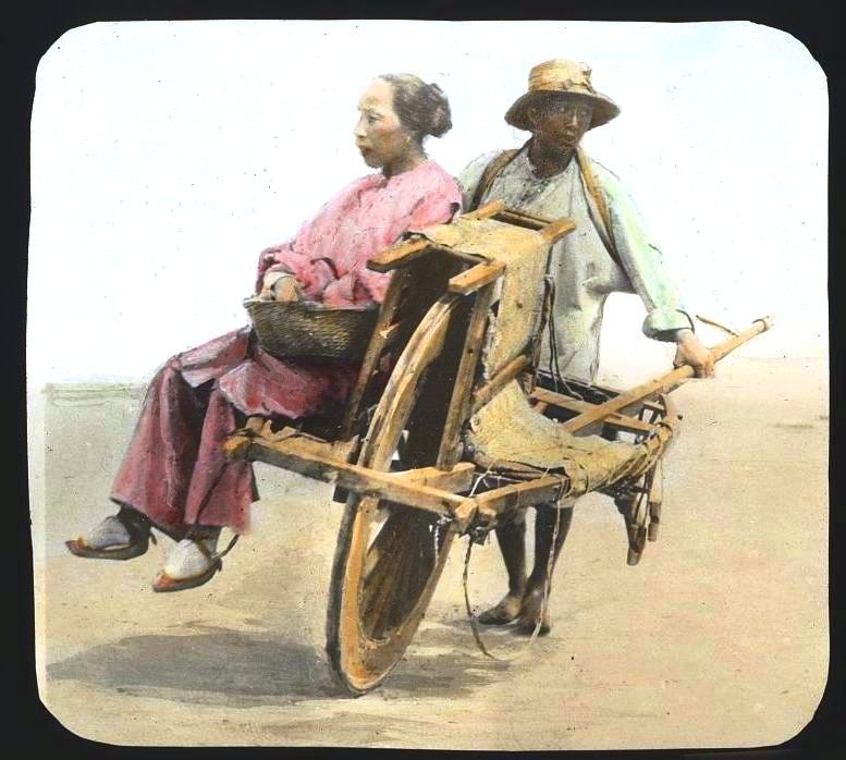 Portrait - Photo - Woman with bound feet being wheeled by man